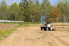 Un mini trattore nel campo della terra Fotografia Stock
