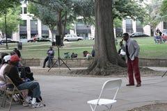 Un ministro de la iglesia que predica a los hombres sin hogar y las mujeres en una ciudad parquean Fotos de archivo libres de regalías