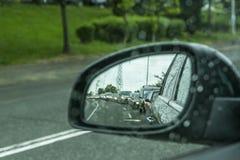 Un miroir latéral d'une voiture dans le temps et les embouteillages pluvieux en gouttes de pluie de foyer de la voiture images libres de droits