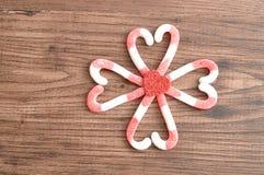 Un modèle de fleur fabriqué à partir de des cannes de sucrerie a emballé dans des formes de coeur avec un petit coeur rouge Photo libre de droits