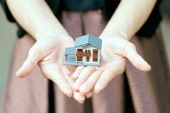 Un modèle modèle de maison est placé sur les mains de la fille asiatique d'affaires utilisation en tant que le concept d'affaires Photo stock