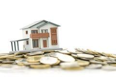Un modèle modèle de maison est placé sur une pile des pièces de monnaie utilisation en tant que le concept d'affaires de fond et  Photos stock