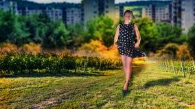 Un modèle femelle marche dans le jardin de vignoble Images stock