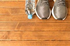 Un mode de vie sain Espadrilles courantes, bouteille d'eau sur en bois Images libres de droits
