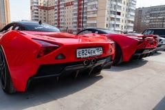 Un modello B1 di due delle automobili motori di Marussia nel colore rosso ed in tetto nero e nella retrovisione delle ruote Fotog fotografia stock
