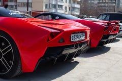 Un modello B1 di due delle automobili motori di Marussia nel colore rosso ed in tetto nero e nella retrovisione delle ruote Fotog immagini stock