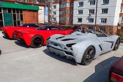 Un modello B1 di tre delle automobili motori di Marussia nel colore rosso ed in tetto nero e nella retrovisione delle ruote Fotog fotografie stock