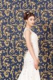 Un modello castana attraente in un vestito da sposa bianco che sta su un fondo blu della parete con un modello dell'oro Fotografia Stock