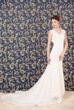 Un modello castana attraente in un vestito da sposa bianco che sta su un fondo blu della parete con un modello dell'oro Immagine Stock