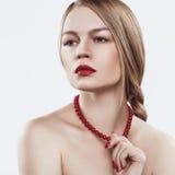 Un modello con capelli biondi intrecciati in una treccia, in una pelle giusta, nelle spalle nude ed in una collana rossa sul coll Fotografie Stock