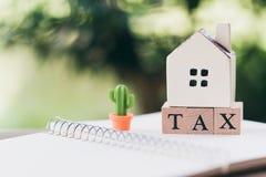 Un modello di modello della casa è disposto sulla parola di legno TASSA come concetto del bene immobile della proprietà del fondo immagine stock libera da diritti