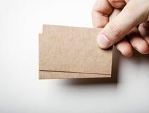Un modello di due carte di impresa artigiana ed equipaggia la mano Immagine Stock