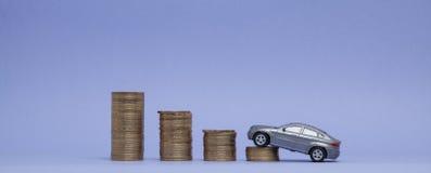 Un modello grigio di una macchina con le monete sotto forma di istogramma su un fondo porpora Concetto del prestito, risparmio, a Fotografia Stock Libera da Diritti