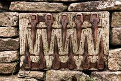 Un modello insolito di vecchio insieme di strumenti dell'azienda agricola in una parete di pietra immagine stock libera da diritti