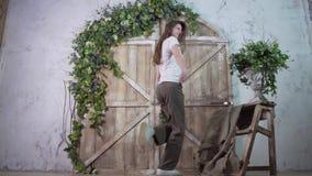 Un modelo alto presenta y baila activamente con una sonrisa contra la perspectiva de un photozone de madera almacen de metraje de vídeo