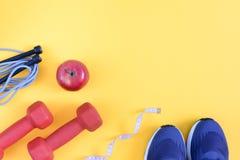 Un modelo con un lugar para el texto en un tema de los deportes Fondo de la aptitud Pesas de gimnasia, zapatillas de deporte, una Fotografía de archivo