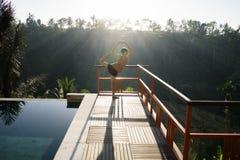 Un modelo de una mujer hermosa, de pelo corto y joven que hace yoga con las actitudes de Natarajasana por la piscina con vistas d fotos de archivo libres de regalías