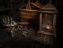 Un modelo de veleros, un tronco con las decoraciones y una linterna con una cesta Imagen de archivo libre de regalías