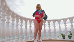 Un modelo embarazada acertado se está colocando en un traje de baño en el balcón y la presentación metrajes