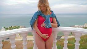 Un modelo embarazada acertado se está colocando en un traje de baño en el balcón y la presentación almacen de metraje de vídeo