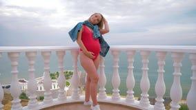 Un modelo embarazada acertado se está colocando en un traje de baño en el balcón y la presentación almacen de video