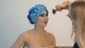 Un modelo hermoso participa en una sesión de foto Los artistas de maquillaje utilizan los cepillos especiales para el polvo enton almacen de metraje de vídeo