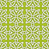 Un modelo ornamental inconsútil basado en nudos cuaternarios célticos en fondo verde Foto de archivo