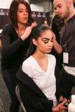 Un modelo que consigue listo entre bastidores en el desfile de moda del FTL Moda durante la caída 2015 de MBFW Imagenes de archivo