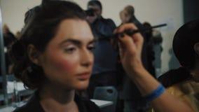 Un modelo tiene su maquillaje hecho entre bastidores durante semana ucraniana de la moda metrajes