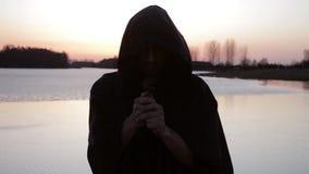 Un moine prie sur le rivage du lac, tenant une croix banque de vidéos
