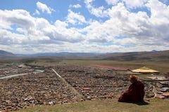 Un moine tibétain donnant sur le Yarchen Gar Yaqen Orgyan Temple images libres de droits