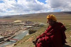 Un moine tibétain donnant sur le Yarchen Gar Yaqen Orgyan Temple photos stock