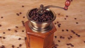 Un molino de café llenado de los granos de café Amoladora de café con los granos de café Amoladora de café manual metrajes