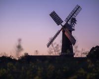 Un molino de trabajo en la puesta del sol Fotos de archivo