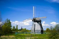 Un molino de viento en un fondo del cielo azul Imagen de archivo libre de regalías