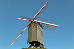 Un molino de viento viejo que se sienta en el top de una colina en una pequeña ciudad en Bélgica Fotos de archivo