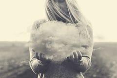 Un momento surrealista, mujer solitaria que sostiene en sus manos una nube gris fotografía de archivo libre de regalías