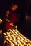 Un monaco buddista accende le lampade del burro Immagini Stock
