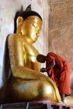 Un monaco vicino ad una grande statua di Buddha Tempio di Sulamani Bagan myanmar immagini stock