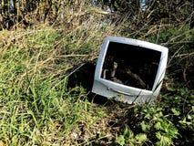 Un monitor de computadora viejo y anticuado que se ha descargado en tierra en inclinar de una mosca o imagen inútil del concepto imagen de archivo