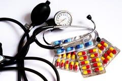 Un monitor y medicinas de la presión arterial en diversas cápsulas coloreadas Imagenes de archivo