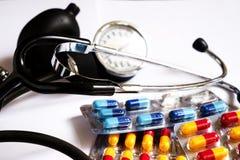 Un monitor y medicinas de la presión arterial en diversas cápsulas coloreadas Fotos de archivo libres de regalías