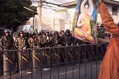 Un monje aumenta una imagen de Buda para convencer al ejército del alboroto Foto de archivo libre de regalías