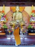 Un monje que ruega la estatua de Buda entre las flores Fotografía de archivo