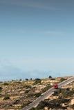 Un monospace rouge entraînant une réduction une colline dans la campagne maltaise, ju photos stock