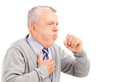 Un monsieur mûr toussant en raison de la maladie pulmonaire Images stock