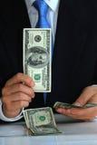 Un monsieur retenant la facture $100 aime renverser le pl Image stock