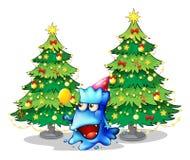 Un monstre près des arbres de Noël verts de pin Image stock