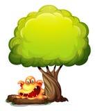 Un monstruo anaranjado asustadizo debajo del árbol Foto de archivo libre de regalías
