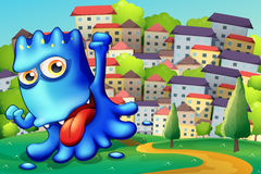 Un monstruo azul presumido sobre la colina a través de los edificios Fotos de archivo